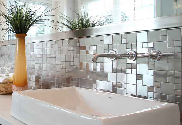 Close-up of sink with small tiled backsplash in executive home.