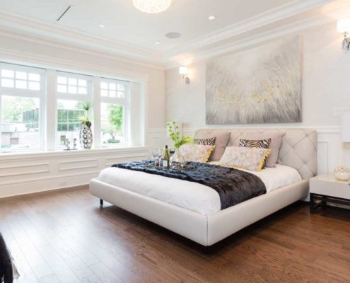 Bright white master bedroom with black and yellow accents.