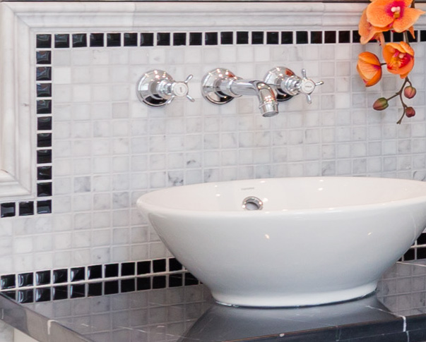 Close-up of sink with small tiled backsplash.
