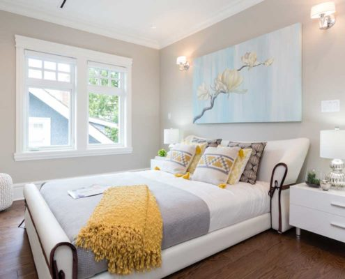 White on white bedroom with splashes of yellow accents.