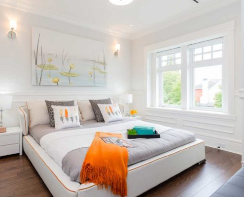 White on white bedroom with splashes of orange accents.