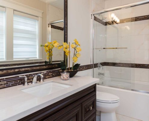Guest bathroom with brown cabinets and white marble counter tops.
