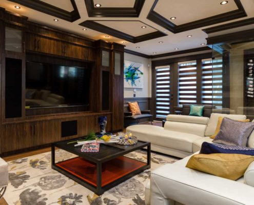 Dramatic tray ceiling and plantain shutter complete entertainment area.