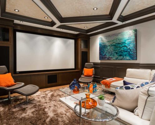 Wood panelled media room with tray ceiling.