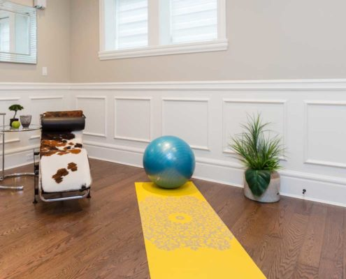 At-home workout room with yoga mat and cow skin covered chair.