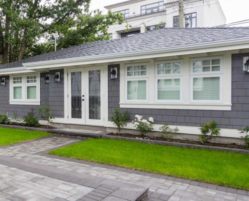 Grey shingled one story guest house with white trim.