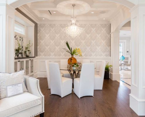 White and silver dining room with large chandelier.