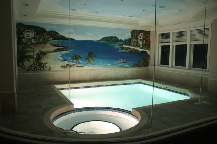 Indoor swimming pool with seascape mural.