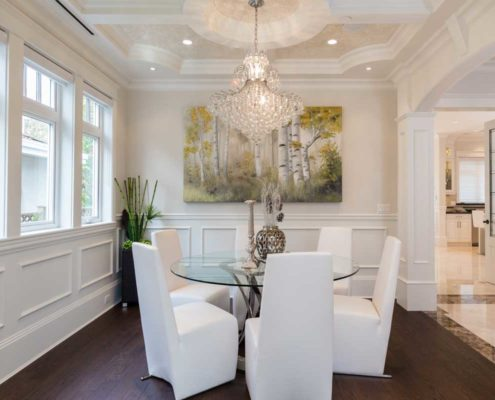 White dining room with large chandelier.
