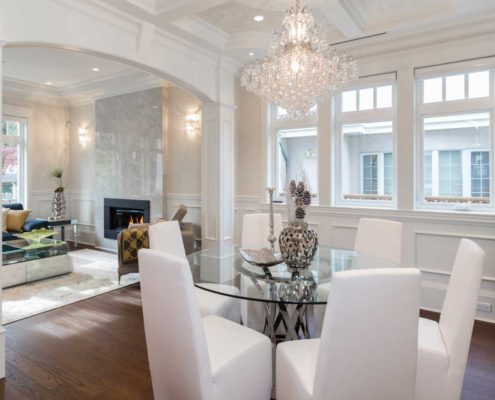 White dining room with large chandelier and looking into living room.