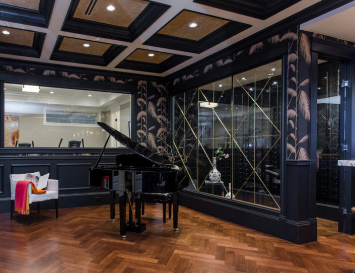 Recreation room with grand piano and wine storage.