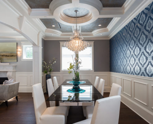 Formal dining room with blue wallpaper and large chandelier.