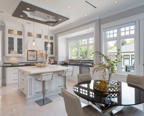 Bright white kitchen with tray ceiling and sitting area.