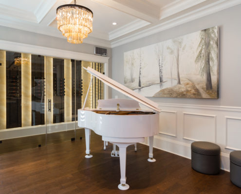 White grand piano in front of glassed-in wine cellar.