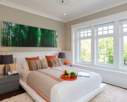 Bedroom in craftsman styled home with large woodsy painting over bed.