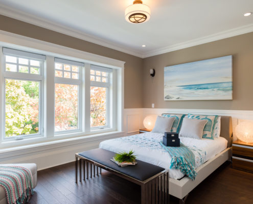 Bedroom in craftsman styled home with large ocean painting over bed.