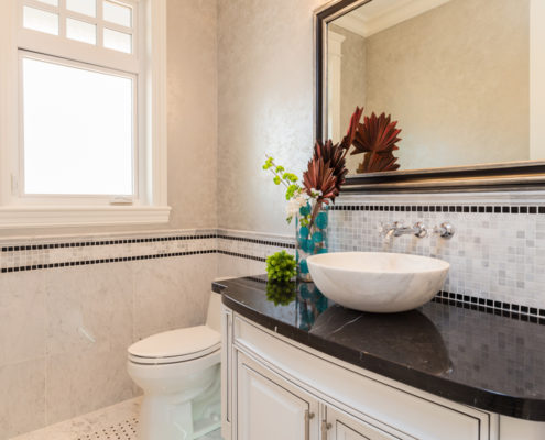 Bath with stunning tile work and black marble countertop..