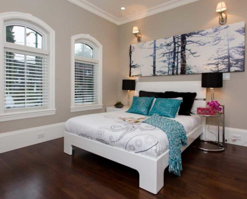 Bedroom in classic home with white linens and blue accents.