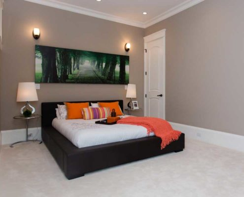 Bedroom in classic home with white linens and orange accents.