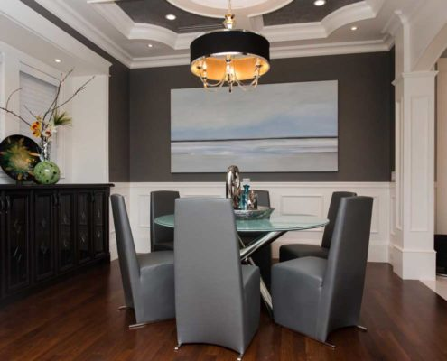 Stylish modern dining room with round table and sleek grey leather chairs.