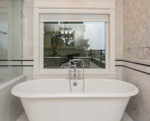 Stand alone bath tub in front of large window.