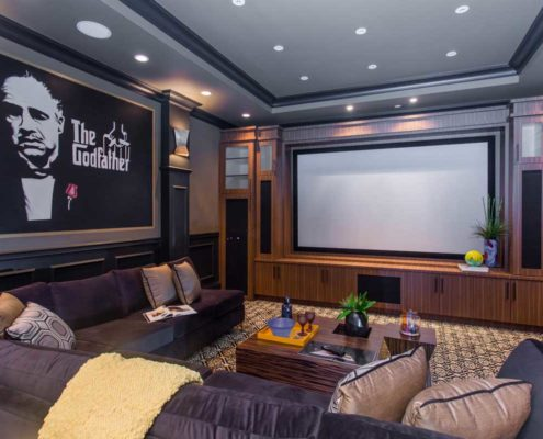 Dramatic entertainment room with large movie screen and The Godfather movie poster.