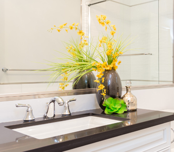 Close-up of under mount sink with rich black marble countertop.